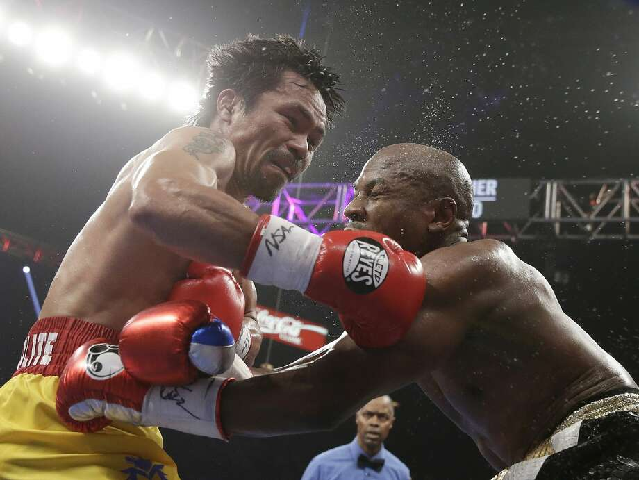 Manny Pacquiao, from the Philippines, left, trades blows with Floyd Mayweather Jr., during their welterweight title fight on Saturday, May 2, 2015 in Las Vegas. (AP Photo/Isaac Brekken)
