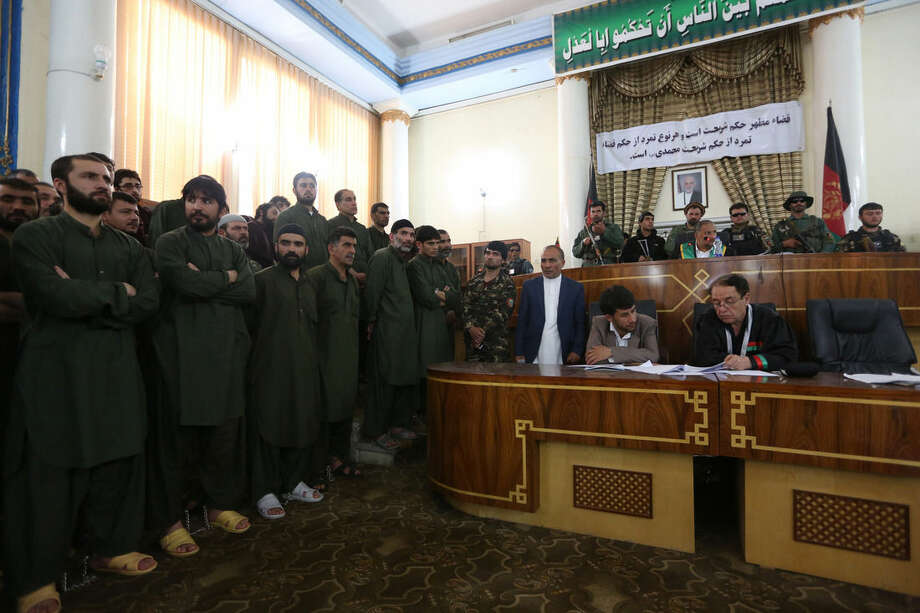 Defendants left, attend their trial at the Primary Court in Kabul, Afghanistan, Saturday, May 2, 2015. The trial of 49 suspects, including 19 police officers, on charges relating to the mob killing of an Afghan woman began in the capital, Kabul, on Saturday. The opening of the trial at Afghanistan's Primary Court was broadcast live on nationwide television. The suspects all face charges relating to the March 19 killing of a 27-year-old woman named Farkhunda. (AP Photo/Rahmat Gul)