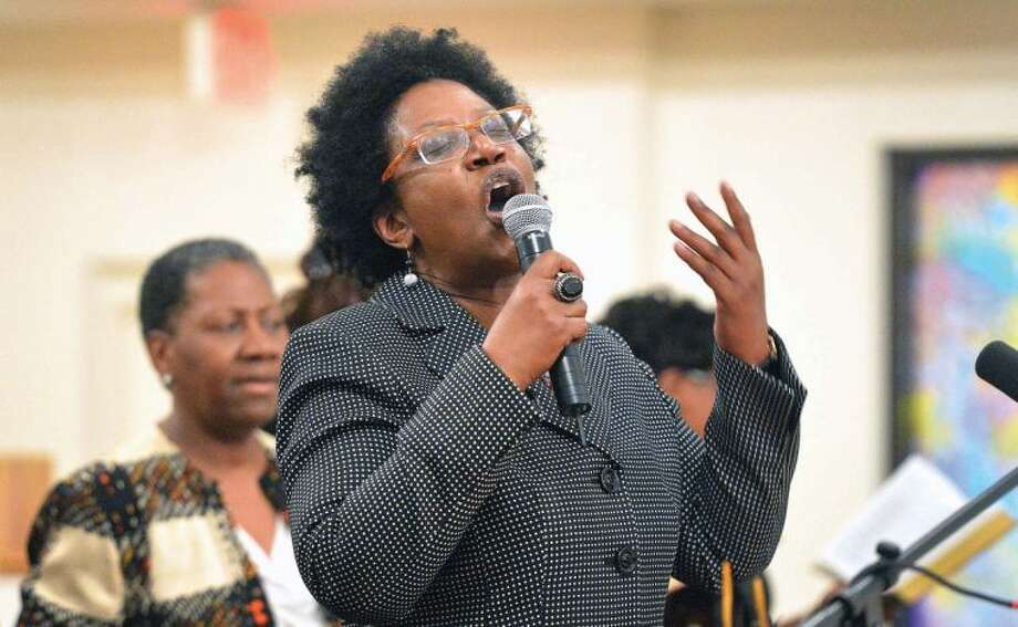 Hour Photo/Alex von Kleydorff . Reverend Dawn C. Snell leads the Friendship Baptist Church of Stamford in the song, Near The Cross, during a a special service, 'Seven Women at The Cross' on Wednesday night