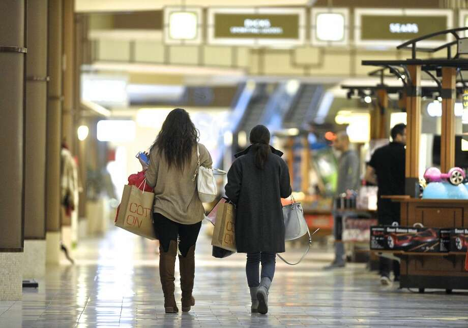 Holiday shoppers with their arms full of shopping bags make their way through the Danbury Fair Mall on Tuesday night, November 24, 2015, in Danbury, Conn.