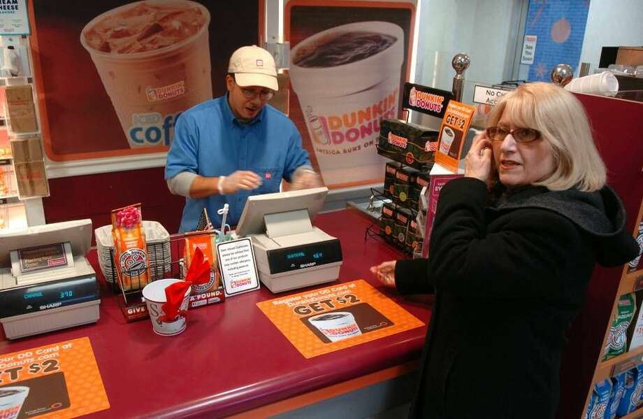 Dunkin Donuts customer Dee Vecchione, of Stratford, at right, learns about the closing of the store from employee Pedro Nieves, in downtown Milford, Conn. on Tuesday Dec. 29, 2009. The shop will be closing due to lease trouble with the building's owner.