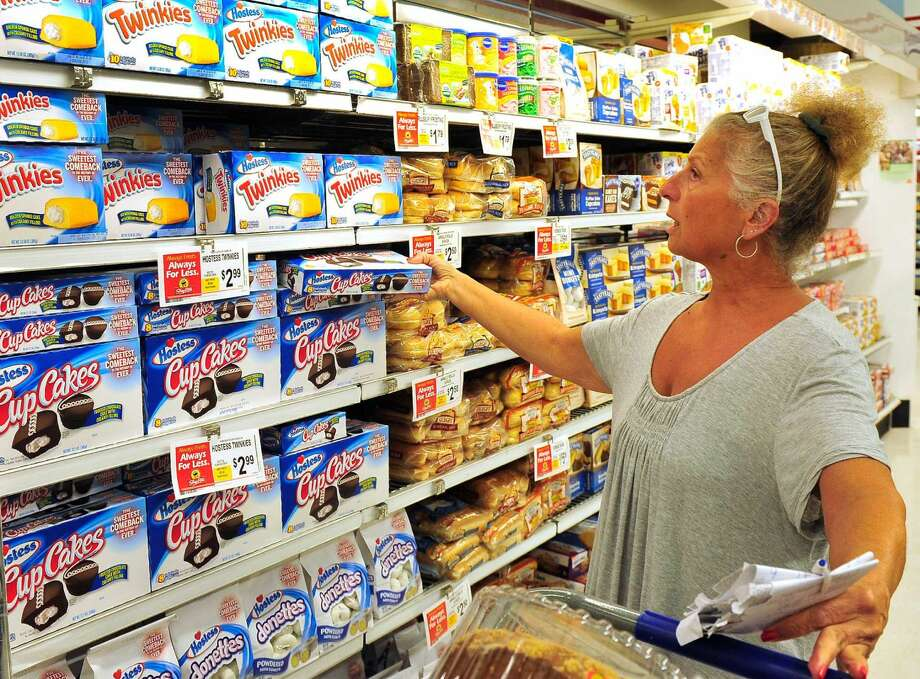 Maureen Osvalda, of New Milford, reaches for Hostess Cup Cakes which are back on the shelves at ShopRite in Brookfield, Conn. Monday, July 15, 2013. She says her husband will be thrilled.