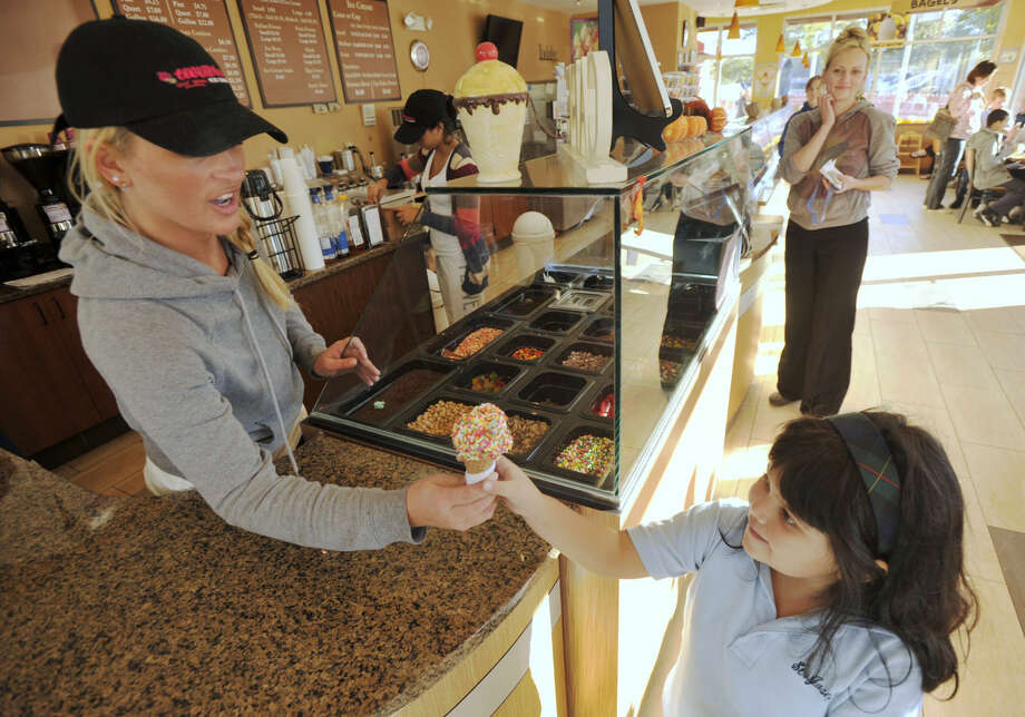 Caitlin Hart, left, gives Maya Jager her ice cream during St. Joseph School's Blue Ribbon Ice Cream Night at Dubl Twister in Danbury on Thursday, Oct. 11, 2012.