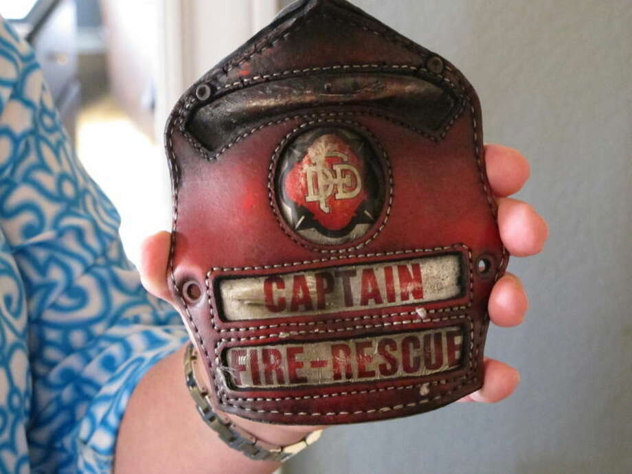 In this April 9, 2014 photo Holly Harris holds a badge that belonged to her husband, Dallas Fire-Rescue Capt. Kenneth Luckey Harris, at her home outside West, Texas. Kenneth Harris was one of 15 people killed in a deadly explosion at West Fertilizer Co., that still raises questions in the community one year later about what happened. (AP Photo/Nomaan Merchant)