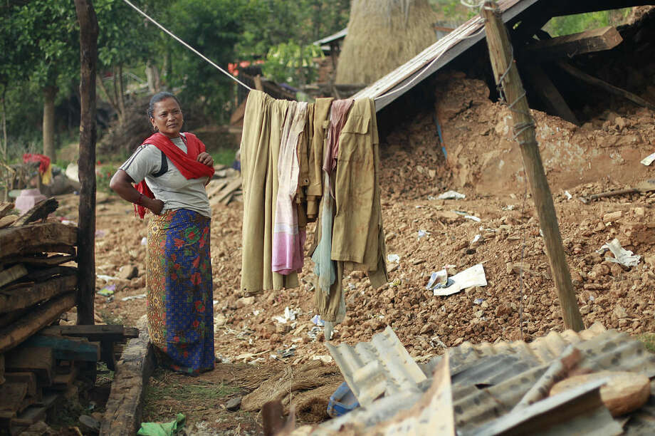 In this photo taken on Saturday, May 2, 2015, standing in the rubble of her home, Radha Shrestha, 42, strings a clothesline to hang laundry in the destroyed village of Pokharidanda, near the epicenter of the April 25 massive earthquake, in the Gorkha District of Nepal. People in villages reachable by road in Nepal's quake-wracked central Gorkha District are fending for themselves, with the government so short on relief they've been forced to focus only on far-flung reaches of the remote Himalayas. (AP Photo/Wally Santana)