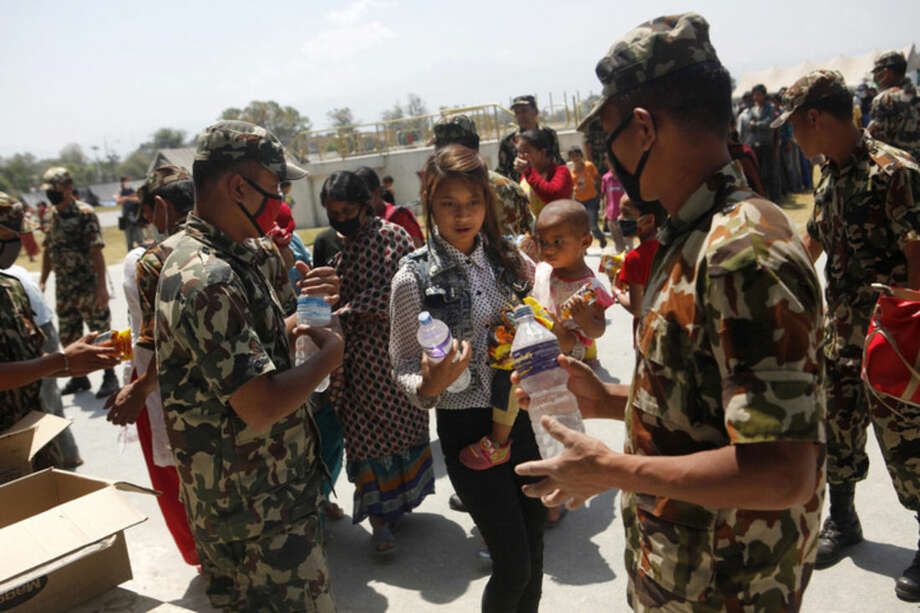 Nepalese army soldiers distribute drinking water and packed noodles for the people who have had their homes damaged and are living in tents after the April 25 earthquake in Kathmandu, Nepal, Sunday, May 3, 2015. With monsoon rains expected in a few weeks, Nepal has pleaded with donors to send tents and temporary shelters for earthquake victims who have been living in the open for more than a week, with their homes damaged by the quake. (AP Photo/Niranjan Shrestha)