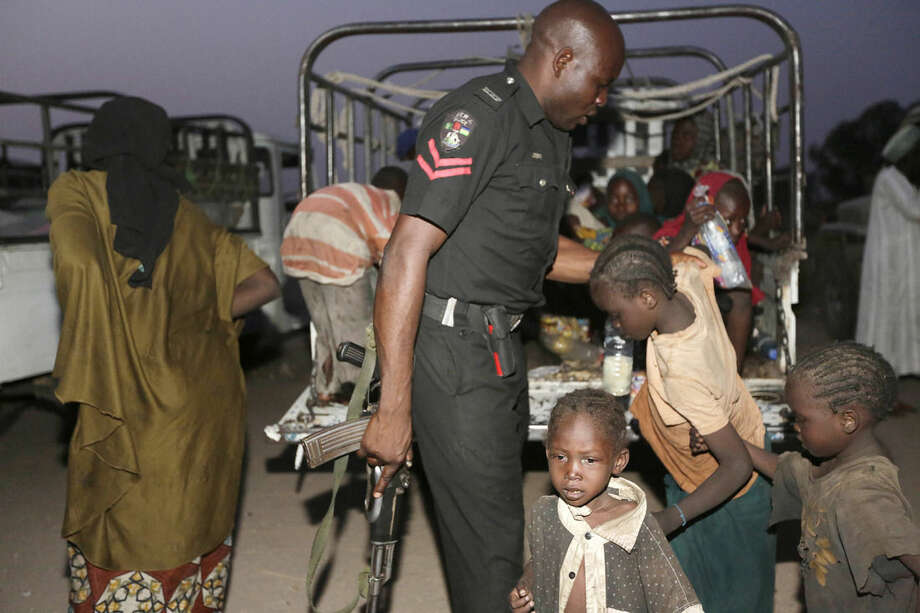 A Nigerian police officer helps children who were rescued by Nigerian soldiers from Boko Haram extremists at Sambisa Forest to get off a truck upon their arrival at a refugee camp in Yola, Nigeria, Saturday May 2, 2015. They were among a group of 275 people rescued from Boko Haram extremists, the first to arrive at the refugee camp Saturday after a three-day journey to safety. Nigerian military said it has rescued more than 677 girls and women and destroyed more than a dozen insurgent camps in the past week. (AP Photo/Sunday Alamba)