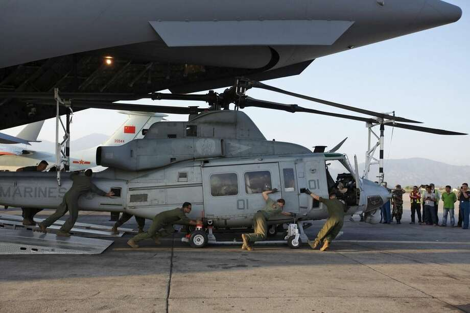 US soldiers unload Huey helicopters from a US Air Force Boeing C-17 Globemaster III after the same landed at the Tribhuvan International Airport in Kathmandu, Nepal, Sunday, May 3, 2015. The aircraft brought in much needed rescue helicopters to fly relief materials and medicine to remote mountainous villages affected by the April 25 earthquake. (AP Photo/Niranjan Shrestha)