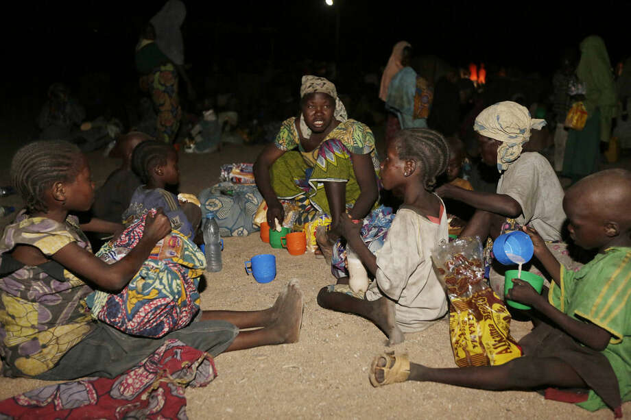Women and children rescued by Nigerian soldiers from Boko Haram extremists at Sambisa Forest eat a meal together after arriving with others at a refugee camp in Yola, Nigeria Saturday, May 2, 2015. They were among a group of 275 people rescued from the Islamic extremists, the first to arrive at the refugee camp Saturday after a three-day journey to safety. The Nigerian military said it has rescued more than 677 girls and women and destroyed more than a dozen insurgent camps in the past week. (AP Photo/Sunday Alamba)