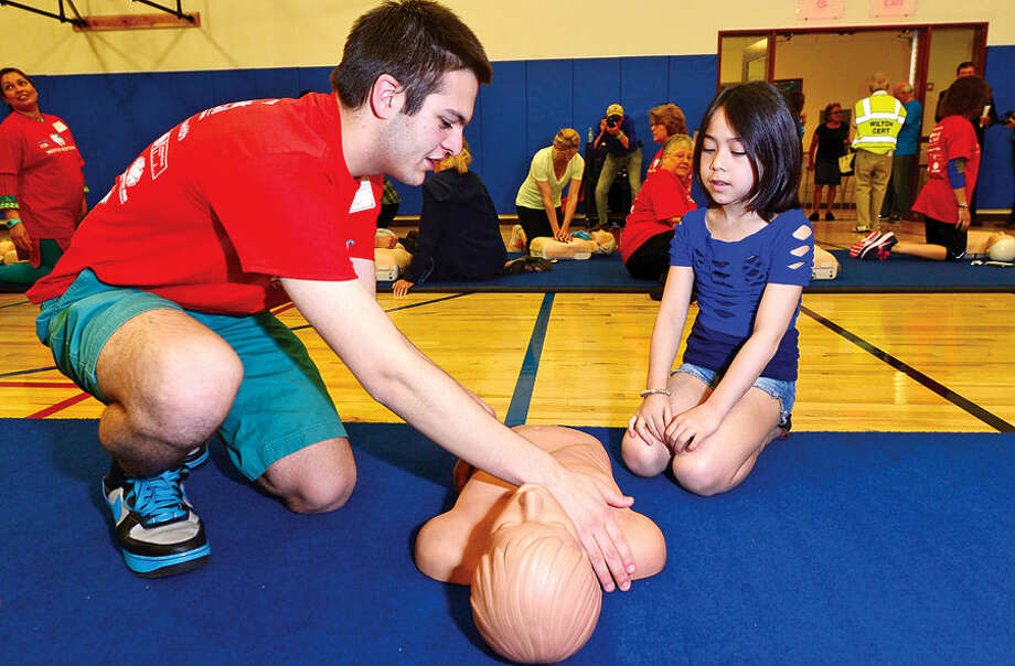 Hour photo / Erik Trautmann Westport EMT and Hands for Life volunteer Ben Muller teaches Aimee Millman the proper CPR technique during the annuls Hands for Life CPR event at the Westport Weston YMCA Sunday.