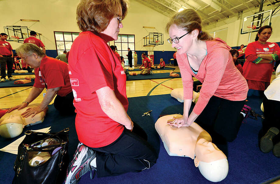 Hour photo / Erik Trautmann Penny Maxwell in taught CPR by Norwalk Hospital employee and Hands for Life volunteer Mary Poudreau during the annual hands for Life CPR traing event at the new Westport Weston YMCA Sunday.