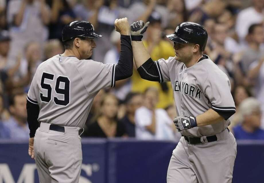 New York Yankees' Brian McCann, right, high-fives third base coach Rob Thomson (59) after hitting a fifth-inning home run off Tampa Bay Rays starting pitcher David Price during a baseball game on Thursday, April 17, 2014, in St. Petersburg, Fla. (AP Photo/Chris O'Meara)
