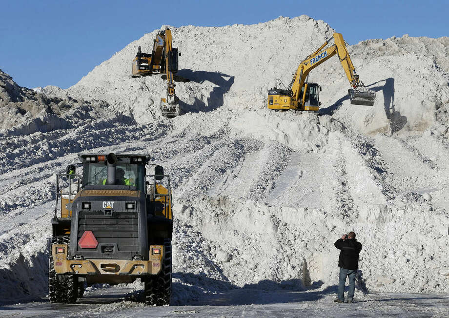 "FILE - In this Feb. 16, 2015 file photo, heavy equipment works at a ""snow farm"" on a mound of snow from roads cleared in Boston. More than $1 billion was spent and 6 million tons of salt used to keep highways operating in nearly two dozen states during the recent harsh winter, according to a first-ever survey of state transportation officials. (AP Photo/Michael Dwyer, File)"