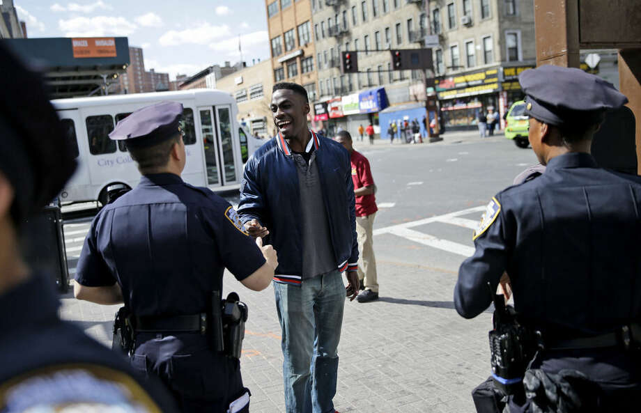 Police officers talk with a pedestrian on 125th Street in the Harlem section of New York, Wednesday, April 29, 2015. (AP Photo/Seth Wenig)