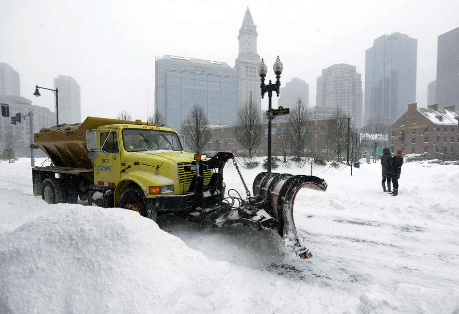 FILE - In this Jan. 27, 2015 file photo, aA snowplow clears a street near Quincy Market in Boston. More than $1 billion was spent and 6 million tons of salt used to keep highways operating in nearly two dozen states during the recent harsh winter, according to a first-ever survey of state transportation officials. (AP Photo/Steven Senne, File)