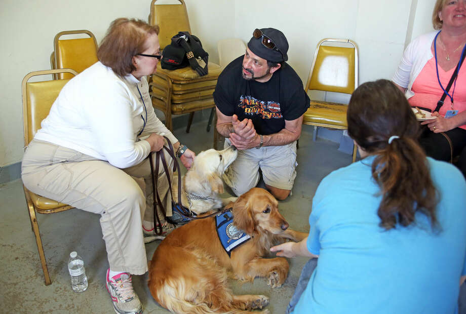 Robert Robinson talks to the LCC K-9 Comfort Dog Ministry during the 3rd annual Pony Rides For A Purpose event to benefit the Jessica Rekos Foundation at the The 2nd Company Governor's Horse Guard in Newtown, CT Sunday afternoon. Hour Photo / Danielle Calloway