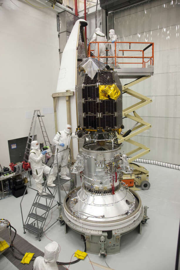 In this Aug. 20, 2013 photo provided by NASA, engineers prepare to install the Lunar Atmosphere and Dust Environment Explorer (LADEE) spacecraft into the fairing of the Minotaur V launch vehicle nose-cone at NASA's Wallops Flight Facility in Wallops Island, Va. On Friday, April 18, 2014, flight controllers confirmed that the orbiting spacecraft crashed into the back side of the moon as planned, just three days after surviving a full lunar eclipse, something it was never designed to do. During its $280 million mission, LADEE identified various components of the thin lunar atmosphere — neon, magnesium and titanium, among others — and studied the dusty veil surrounding the moon, created by all the surface particles kicked up by impacting micrometeorites. (AP Photo/NASA, Terry Zaperach)