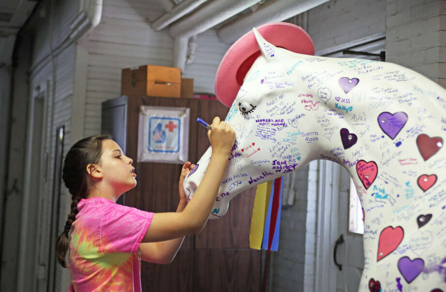 Berit Ostensen, 12, signs a horse for Jessica during the 3rd annual Pony Rides For A Purpose event to benefit the Jessica Rekos Foundation at the The 2nd Company Governor's Horse Guard in Newtown, CT Sunday afternoon. Hour Photo / Danielle Calloway