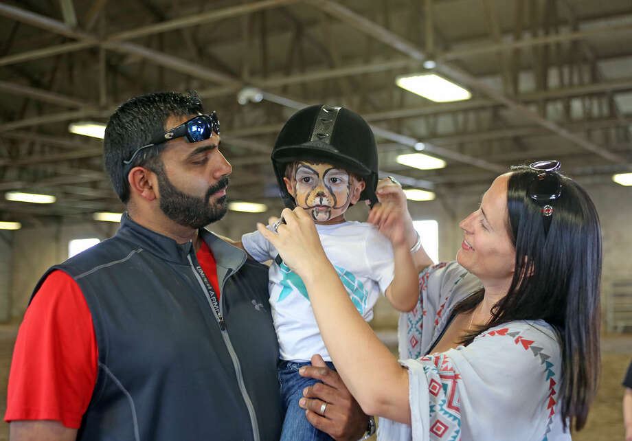 Dhru Ghadiyali prepares to ride a horse with his parents Rinky and Katy during the 3rd annual Pony Rides For A Purpose event to benefit the Jessica Rekos Foundation at the The 2nd Company Governor's Horse Guard in Newtown, CT Sunday afternoon. Hour Photo / Danielle Calloway