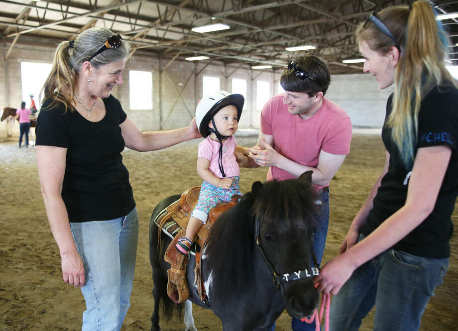 Grace Rothstein, 1, sits on Tyler the minature pony during the 3rd annual Pony Rides For A Purpose event to benefit the Jessica Rekos Foundation at the The 2nd Company Governor's Horse Guard in Newtown, CT Sunday afternoon. Hour Photo / Danielle Calloway