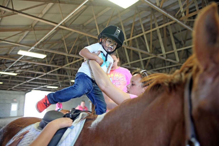Dhru Ghadiyali mounts a horse during the 3rd annual Pony Rides For A Purpose event to benefit the Jessica Rekos Foundation at the The 2nd Company Governor's Horse Guard in Newtown, CT Sunday afternoon. Hour Photo / Danielle Calloway