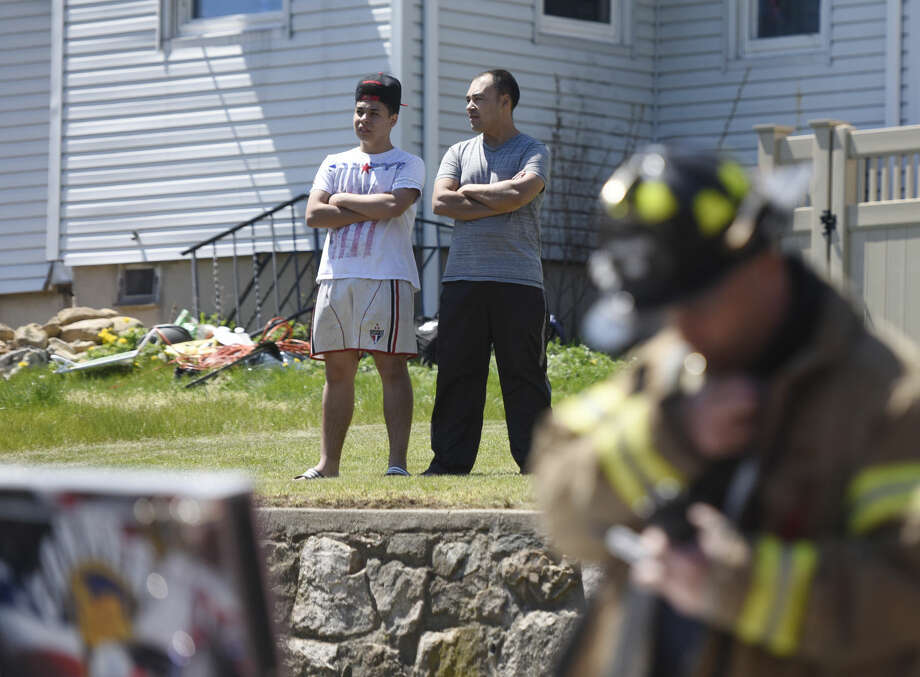 Neighbors watch as Stamford firefighters respond to a house fire at 118 Webb Ave. in Stamford, Conn. Sunday, April 24, 2016.