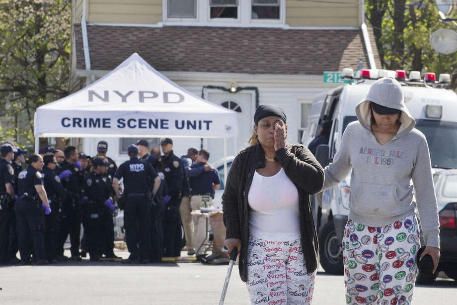 An unidentified woman wipes her face after talking with police officers Sunday, May 3, 2015 about the shooting of a police officer in the Queens borough of New York. Demetrius Blackwell is accused of shooting a New York City police officer in the head Saturday evening and is being charged with two counts of attempted murder of a police officer. (AP Photo/Mark Lennihan)