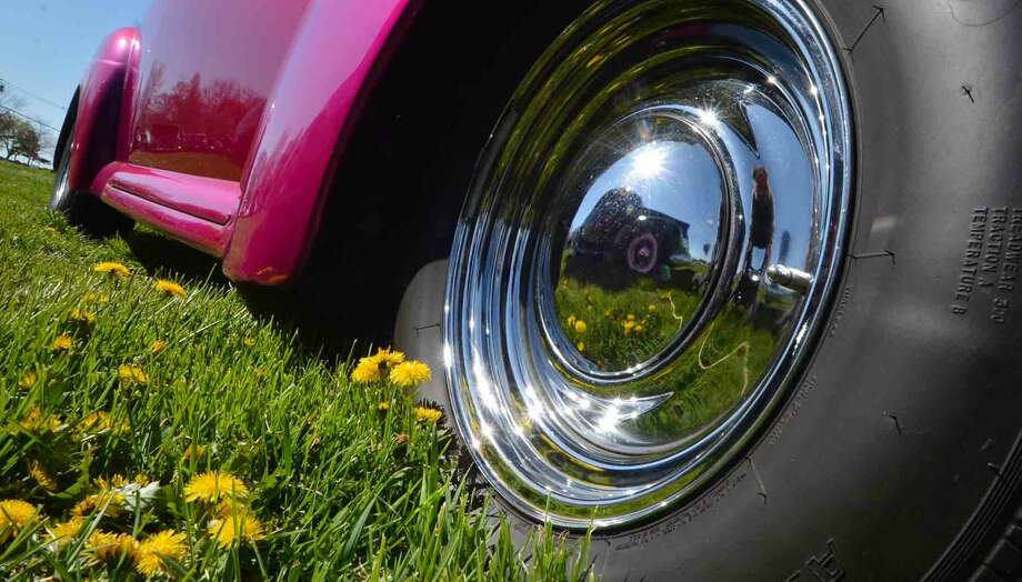 Dandelions in the field are reflected in a hubcap during the 42nd Annual Gateway Antique Auto Show at Taylor Farm on Sunday in Norwalk Conn. April 24 2016