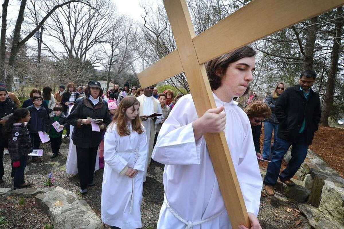 Hour Photo/Alex von Kleydorff. Altar Server Jack Carlan carries the cross during the outdoor Stations of The Cross at St Matthew Church on Good Friday