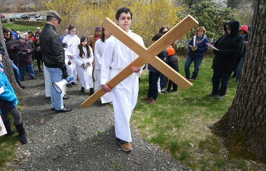 Hour Photo/Alex von Kleydorff Usher Michael Ornato carries the cross and leads parishioner's up a hill and through the garden at St. Matthew's Church during the outdoor Stations of The Cross on Good Friday