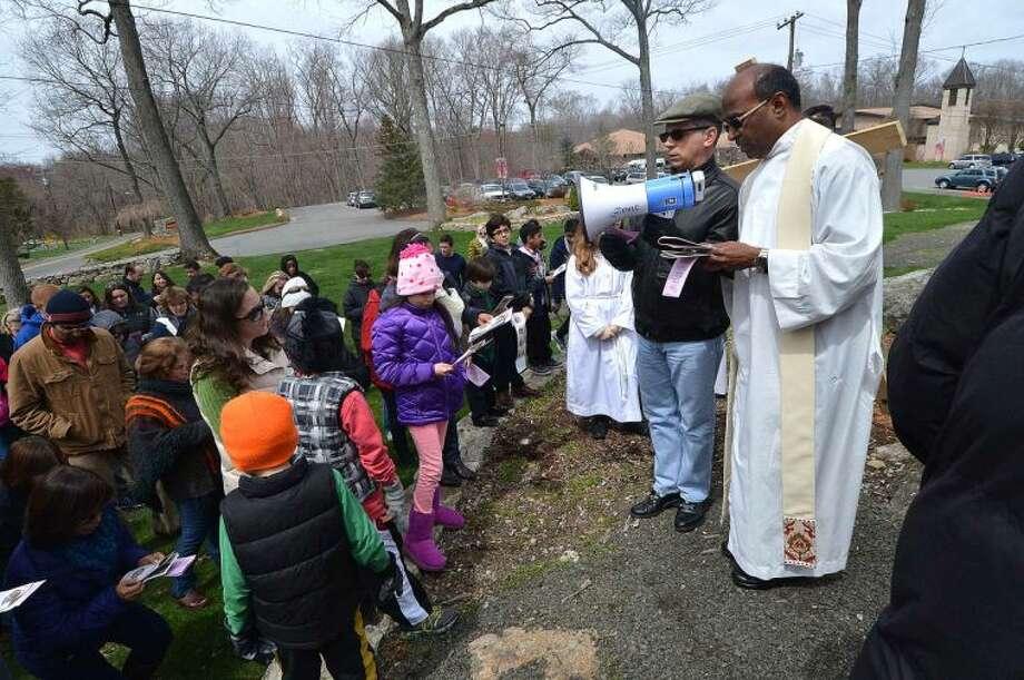 Hour Photo/Alex von Kleydorff Father Paul Sankar leads parishioner's through the garden at St. Matthew's Church during the outdoor Stations of The Cross on Good Friday
