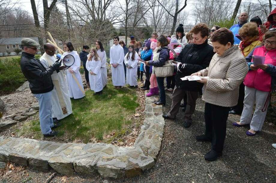 Hour Photo/Alex von Kleydorff Father Paul Sankar leads parishioner's through the garden at St Matthew's Church during the outdoor Stations of The Cross on Good Friday