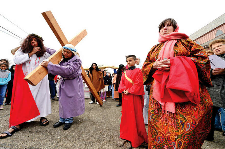 Hour photo / Erik Trautmann Parishioners at St. Josephs Church in South Norwalk follow the Stations of the Cross on Good Friday.