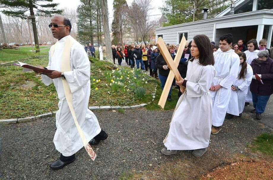Hour Photo/Alex von Kleydorff Father Paul Sankar followed by Alter Server Aimee Whitman carrying the cross, leads parishioner's through the garden at St Matthew's Church during the outdoor Stations of The Cross on Good Friday