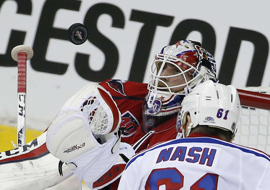 Washington Capitals goalie Braden Holtby (70) prepares to catch the puck with New York Rangers left wing Rick Nash (61) nearby during the third period of Game 3 in the second round of the NHL Stanley Cup hockey playoffs Monday, May 4, 2015, in Washington. The Capitals won 1-0. (AP Photo/Alex Brandon)