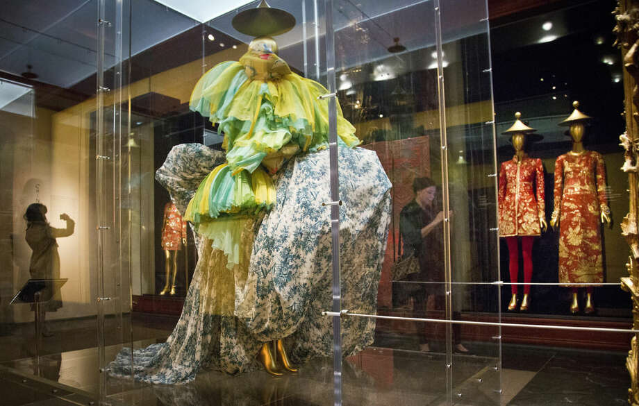 """A 2003 haute couture ensemble from designer John Galliano, left, shares space with a 1996-97 Karl Lagerfeld designed dress and evening gown pair, right, on display during the press preview for the Metropolitan Museum's Costume Institute exhibition """"China: Through the Looking Glass,"""" Monday, May 4, 2015, in New York. (AP Photo/Bebeto Matthews)"""