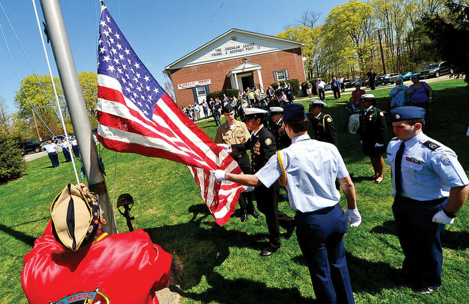Hour photo / Erik Trautmann American Legion Post 12 Seargent at Arms, Dan Caporale, and members of the Norwalh High School ROTC program raise the flag in honor of Army Air Corpsman Joseph P. Lorenti Sr. during a ceremony Sunday.