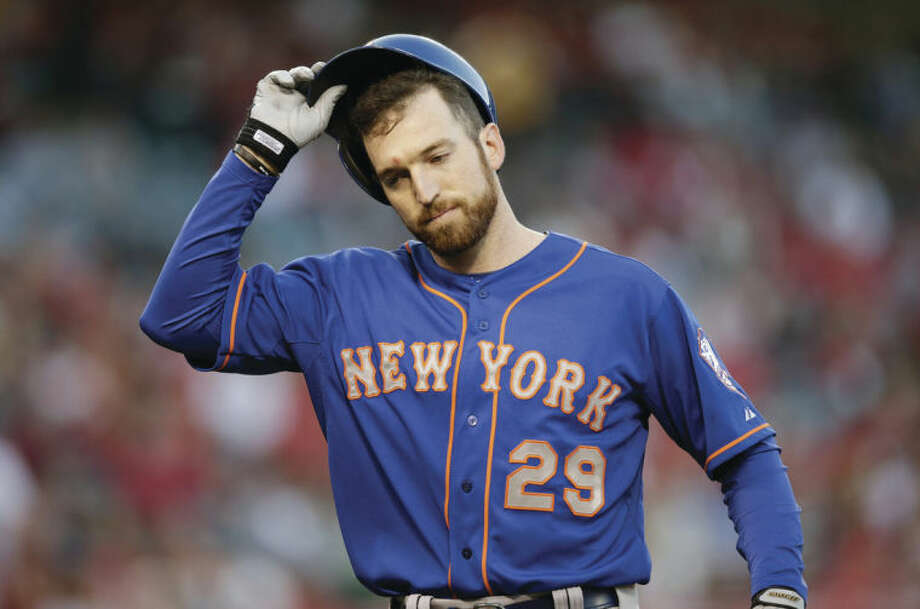New York Mets' Ike Davis takes off his helmet after he flied out during the fourth inning of a baseball game against the Los Angeles Angels on Saturday, April 12, 2014, in Anaheim, Calif. (AP Photo/Jae C. Hong)
