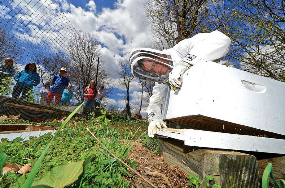 Hour photo / Erik Trautmann Ambler Farm program manager Kevin Meehan puts together a new hive of honey bees Saturday at the farm where they will be part of their summer programming.