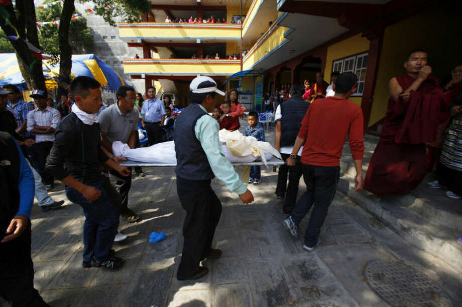 The body of Nepalese mountaineer Ang Kaji Sherpa, killed in an avalanche on Mount Everest, is carried to the Sherpa Monastery in Katmandu, Nepal, Saturday, April 19, 2014. Search teams recovered a 13th body Saturday from the snow and ice covering a dangerous climbing pass on Mount Everest, where an avalanche a day earlier swept over a group of Sherpa guides in the deadliest disaster on the world's highest peak. The Sherpa people are one of the main ethnic groups in Nepal's alpine region, and many make their living as climbing guides on Everest and other Himalayan peaks. (AP Photo/Niranjan Shrestha)