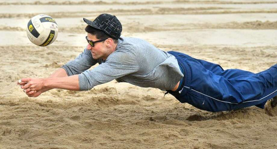 Hour Photo/Alex von Kleydorff Stephen Mackowiak gos for the ball during a friendly game of volleyball in 40 degree weather at Calf Pasture Beach on Friday