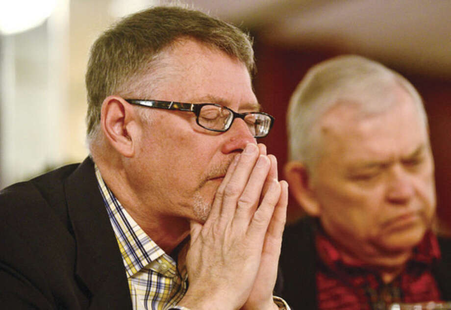 Hour photo / Erik Trautmann Attendees of the Pivot Ministries Prayer Breakfast listen to the opening prayer by the Rev. Richard Williams Friday morning at Continental Manor.