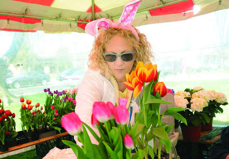 Barbara Oeschger, employee at Izzo's Country Garden in Westport sells East flowers Sunday at St. Thomas the Apostle Church in Norwalk. Hour photo/Matthew Vinci