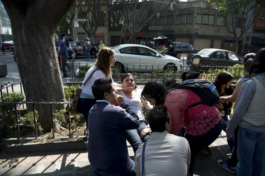 A woman is comforts for others people at the Juarez neighborhood after a strong earthquake jolted Mexico City, Friday, April 18, 2014. The powerful magnitude-7.2 earthquake shook central and southern Mexico but there were no early reports of major damage or casualties, (AP Photo/Eduardo Verdugo)