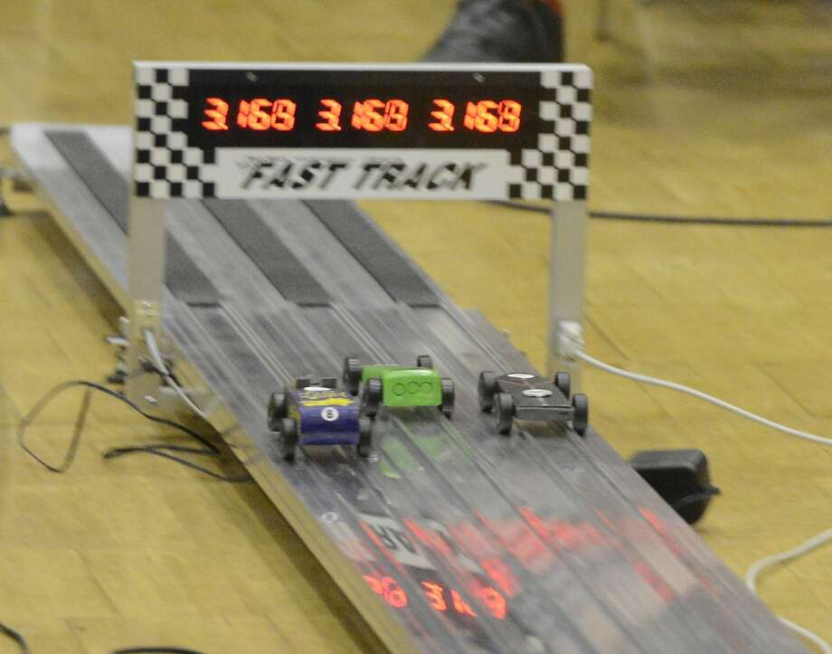 Pine racers speed past the finish during the Powahay District's Pinewood Derby Championship in New Canaan on April 30, 2016.
