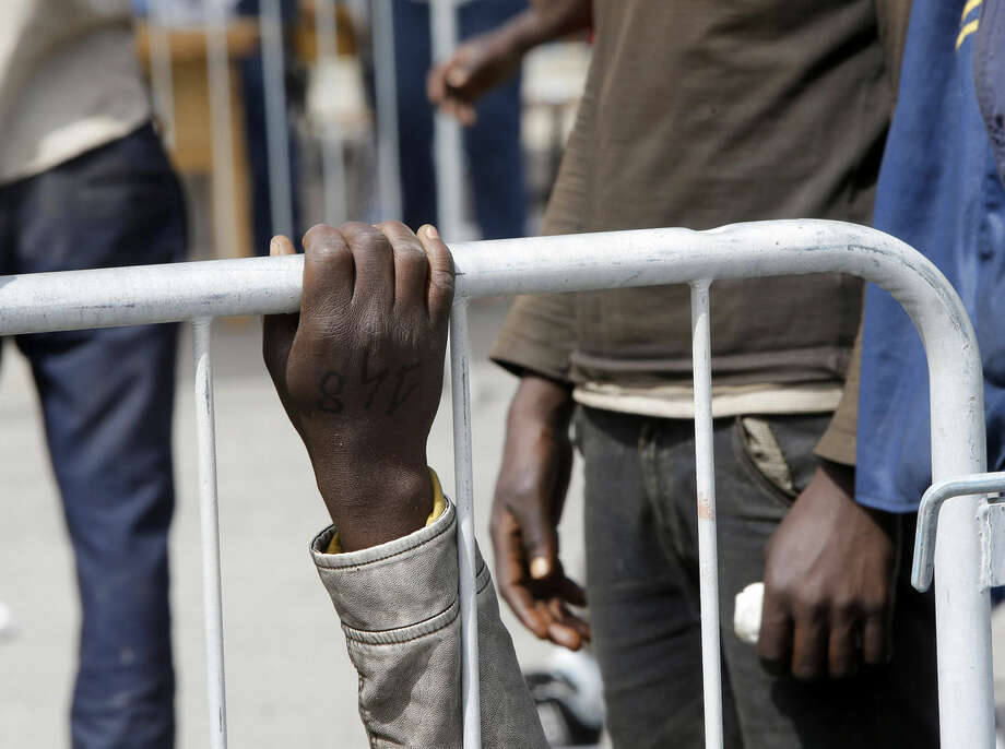 The hand of a migrant grasps a fence after arriving at the Catania harbor, Sicily, southern Italy, Tuesday, May 5, 2015. The arrivals are stretching Italy's already overtaxed migrant reception centers, with new arrivals being sent inland to be screened for asylum or in many cases, to continue on their journeys north unofficially. Dozens of passengers in a crowded rubber boat fell into the sea and likely drowned as a rescue vessel neared, survivors reported as they arrived in Italy Tuesday to join thousands of other migrants rescued in the Mediterranean in recent days. (AP Photo/Antonio Calanni)