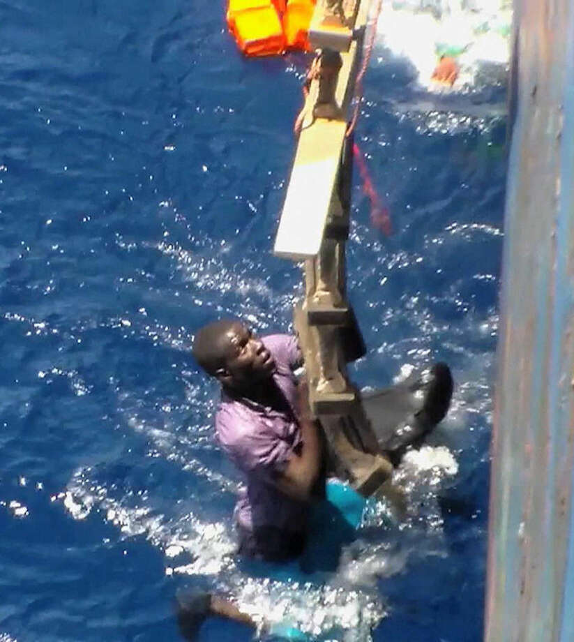 Dramatic footage emerged Tuesday May 5, 2015, filmed by a crew member, showing a Mediterranean Sea rescue of migrants on a sinking rubber boat desperately clambering up ropes and a ladder from the cargo ship Zeran that came to their aid on May 3, 2015, in the sea between Libya and Sicily. Five bodies were recovered and were brought ashore Tuesday along with the migrant survivors to the port in Catania, Sicily, Italy. (AP Photo) TV OUT - NO ARCHIVES