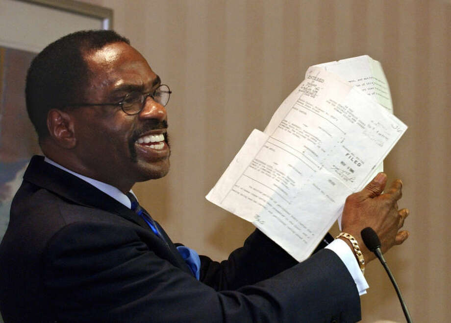 "FILE - In this Jan. 29, 2004 file photo, former boxer, Rubin, ""Hurricane"" Carter, holds up the writ of habeas corpus that freed him from prison, during a news conference held in Sacramento, Calif. Carter, who spent almost 20 years in jail after twice being convicted of a triple murder he denied committing, died at his home in Toronto, Sunday, April 20, 2014, according to long-time friend and co-accused John Artis. He was 76. (AP Photo/Rich Pedroncelli, File)"