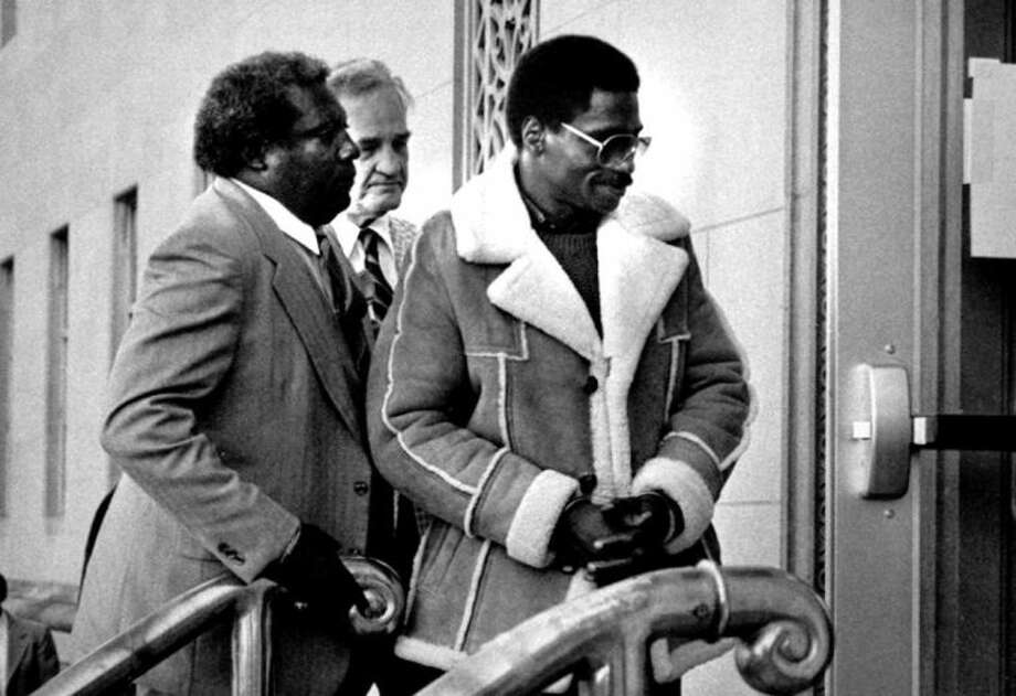 "FILE - In this Nov. 8, 1985 file photo, Rubin ""Hurricane"" Carter, right, the former middleweight boxer, is escorted into federal court in Newark, N.J. Carter, who spent almost 20 years in jail after twice being convicted of a triple murder he denied committing, died at his home in Toronto, Sunday, April 20, 2014, according to long-time friend and co-accused John Artis. He was 76. (AP Photo/File)"
