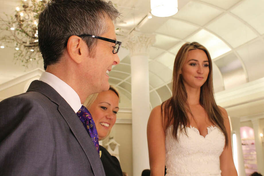 Alyssa Brezovsky trying on a wedding dress with the consultant and Randy Fenoli.